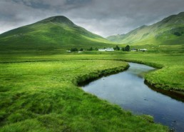 The gentle curve of the river and the light green tones of the grass give this image a calming feel. The montains and the clouds have a less calming effect. Image: courtesy of Icon Photography School - http://www.photographyicon.com/line/